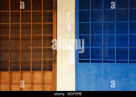 Porte bleue et orange-grille sur la rue. Banque D'Images