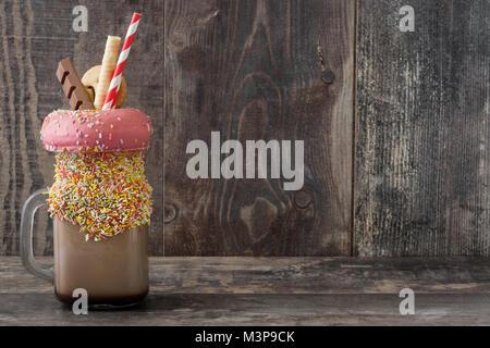 Milk-shake ou extrême freak agiter sur table en bois.