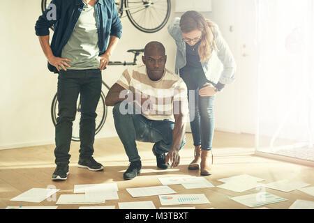 Trois collègues de bureau élégant et moderne en allant sur la paperasse pose sur le sol en face d'eux Banque D'Images