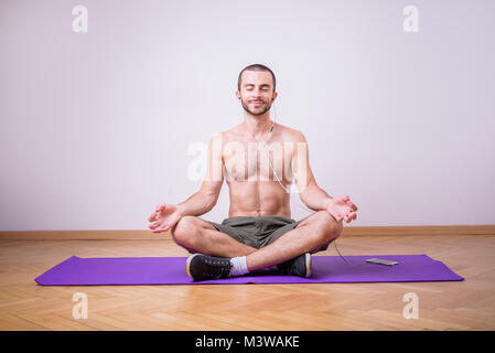 Shirtless man meditating Banque D'Images