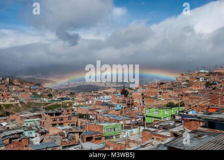 Un arc-en-ciel suspendu dans le ciel bleu sur un bidonville dans le sud de Bogota, Colombie Banque D'Images