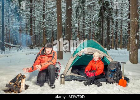Les touristes dans la forêt d'hiver - un homme se réchauffe ses mains par l'incendie Banque D'Images