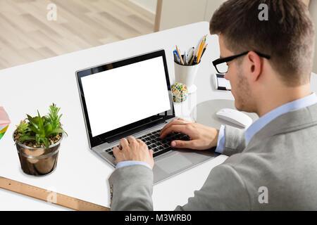 Young Businessman Working On Laptop avec écran blanc Banque D'Images