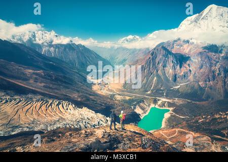 Les hommes debout avec des sacs sur le sommet de la montagne contre la belle vallée de montagne au coucher du soleil. Banque D'Images