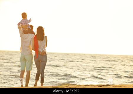 Portrait de famille heureuse et bébé profiter de coucher du soleil à l'été les loisirs Banque D'Images