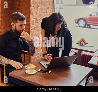Un homme avec des bras tatoués et femelle brune à l'aide d'un ordinateur portable dans un Banque D'Images