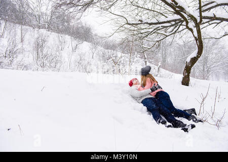 Fille et garçon en jeans et chapeaux tricotés hug à fond blanc Banque D'Images