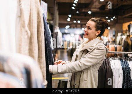 Young attractive woman buying clothes in mall Banque D'Images