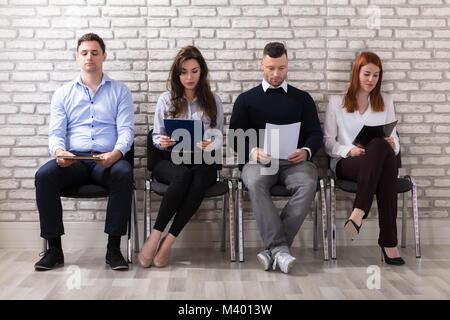 Groupe de gens assis sur une chaise en attente d'Entrevue d'emploi In Office Banque D'Images