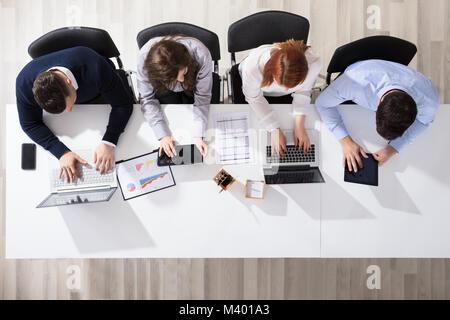Portrait des gens d'affaires à l'aide de dispositifs électroniques At Desk In Office Banque D'Images