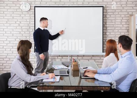 Businessman Giving Presentation de ses collègues en réunion d'affaires Banque D'Images