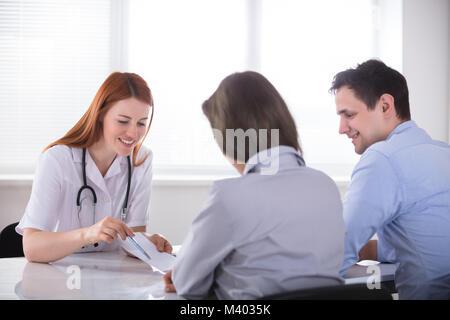 Jeune femme médecin donnant le papier d'ordonnance à un patient dans un centre Banque D'Images