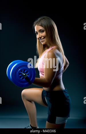 Belle femme avec un sourire sur son visage l'élaboration avec des poids, tandis que sur ses genoux. athlète avec Banque D'Images