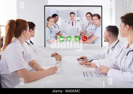 Groupe de professionnels ayant du médecin conférence vidéo en séance Banque D'Images