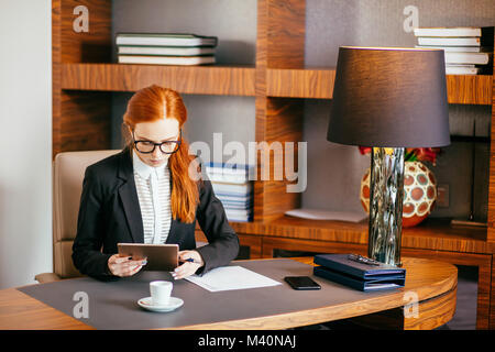 Businesswoman wearing glasses using digital tablet in office Banque D'Images