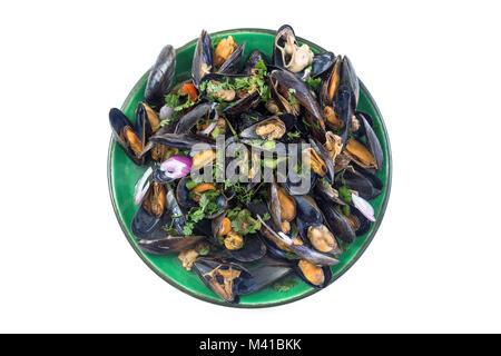 Les moules cuites à la vapeur dans le vin blanc avec des fines herbes, des fruits de mer. Servi dans la plaque verte, sur fond blanc