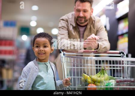 Père et fils faisant épicerie hebdomadaire en boutique Banque D'Images