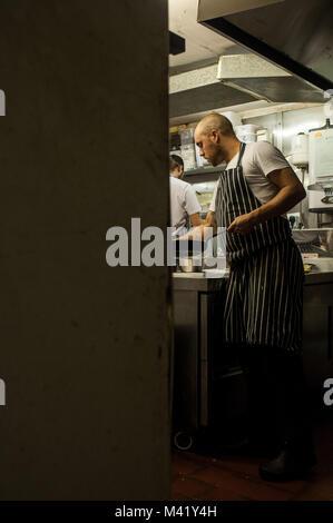 Un chef cuisinier travaillant sur ses pieds dans une cuisine de restaurant à Bristol, Angleterre Banque D'Images