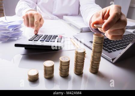 Close-up d'une personne d'affaires à compter des pièces à l'aide d'un ordinateur portable avec calculatrice et documents Banque D'Images