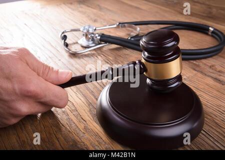 Close-up d'un juge Part Substitution Gavel avec stéthoscope sur un bureau en bois, dans la salle d'audience Banque D'Images