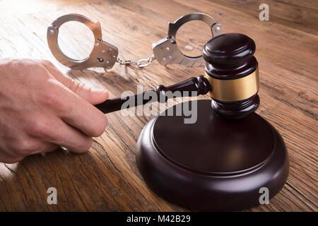Close-up d'un juge Part Substitution Gavel avec des menottes sur un bureau en bois, dans la salle d'audience Banque D'Images