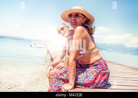 Portrait of mature couple moderne assis sur le maillot d'un dock station. Concept de belles personnes s'amusant Banque D'Images