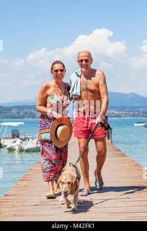 Couple mature en maillot de marcher avec un chien sur le quai d'une station. Concept de belles personnes s'amusant Banque D'Images