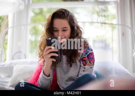 Adolescent dans la chambre looking at smartphone Banque D'Images