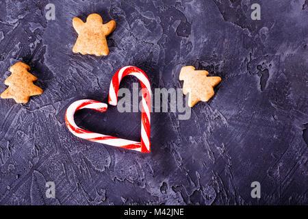 Le rouge et le blanc le Nouvel An bonbons pliée en forme de cœur sur un fond de béton foncé avec des biscuits au Banque D'Images