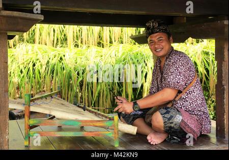 Un homme porte batik Balinais traditionnels chemise et Udeng Rindik casque jouant un instrument de musique traditionnelle. Banque D'Images