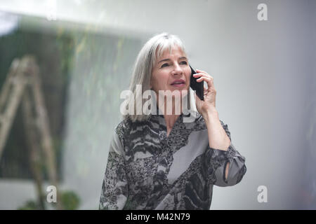 Senior businesswoman sur smartphone Banque D'Images