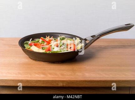 Sauté de style chinois sur une table en chêne haut Banque D'Images
