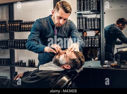 Coiffure élégante la barbe un toilettage dans un saloon. Banque D'Images