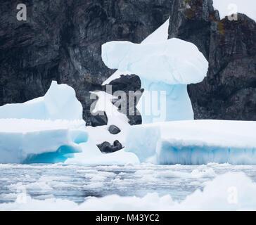 Une étrange formation de glace sur un iceberg bleu clair avec les rochers escarpés de l'Antarctique dans l'arrière Banque D'Images