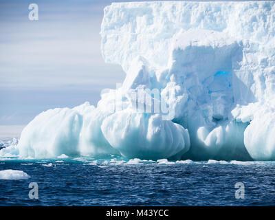 Un grand iceberg bleu clair avec une fondation de sphères. L'eau bleu foncé de l'océan Austral a petites rides. Banque D'Images