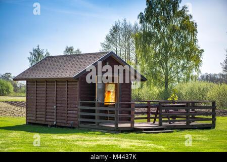 Table de pique-nique sur une terrasse en bois dans un jardin en début de matinée. Une petite maison en bois jaune, Banque D'Images
