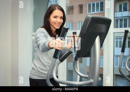 Jeune femme faisant de l'exercice sur un entraîneur elliptique Banque D'Images