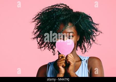 Fille aux cheveux noirs frisés bleuté tenant un cœur rose en face de son visage Banque D'Images