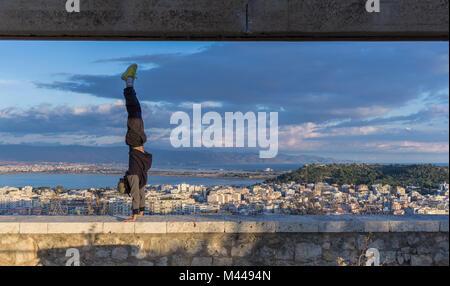 Man doing handstand on wall, Cagliari, Sardaigne, Italie Banque D'Images