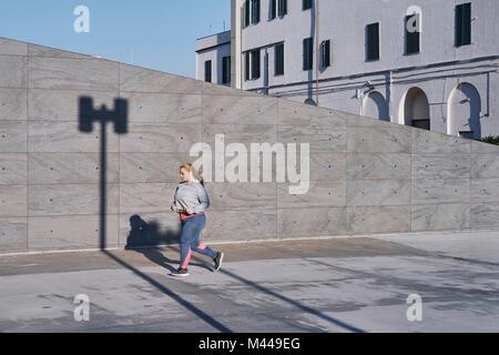 Plantureuse jeune coureuse le long trottoir