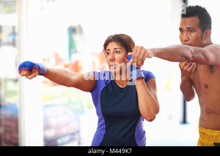 Young woman laying punch boxe avec male trainer in gym Banque D'Images