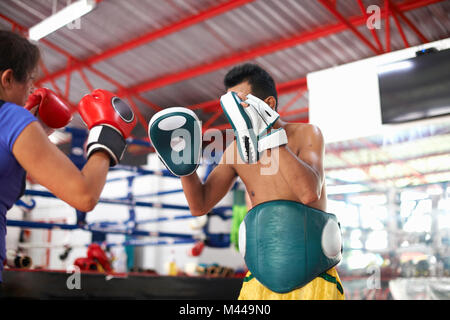 Young woman laying on boxe avec male trainer in gym Banque D'Images
