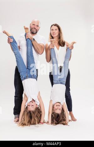 Studio portrait of mature couple avec deux filles faire part se tient, pleine longueur Banque D'Images