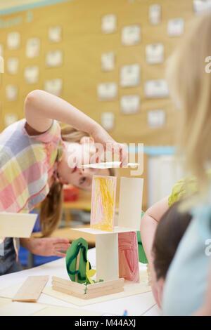 Écolière primaire faire une structure en carton sur un bureau de classe Banque D'Images