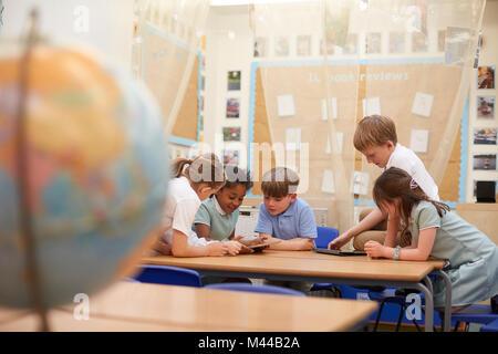 Les écolières et les garçons à la recherche de tablettes numériques en classe à l'école primaire de leçon Banque D'Images