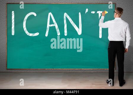 Vue arrière du businessman frottant lettre t de je ne peux pas texte écrit on chalkboard Banque D'Images