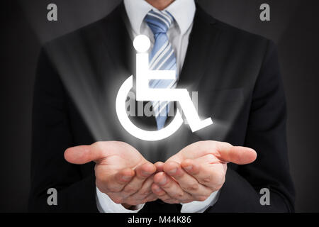 Businessman holding glowing signe d'invalidité dans les mains