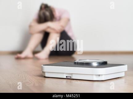 La perte de poids ne concept. Échelle et déprimé, frustré et triste woman sitting on floor holding head et les bras Banque D'Images