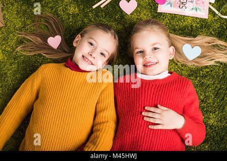 Vue de dessus de Little Sisters lying on carpet entouré avec des coeurs Banque D'Images