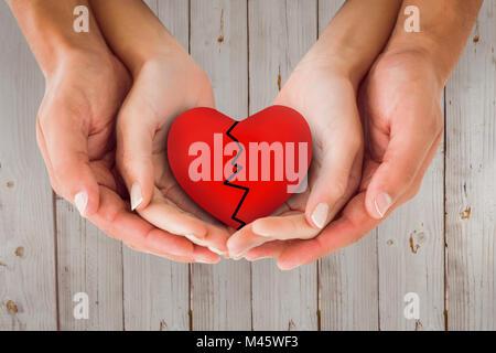 Image composite du couple holding cœur brisé à mains Banque D'Images